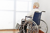 photo of a lady in wheelchair by herself in a corner